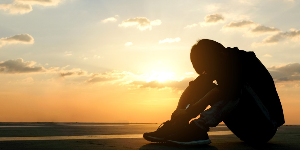 child sitting in sunset with head down