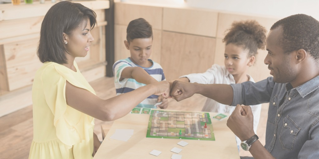 africanamerican-family-playing-board-game-in-cafe-