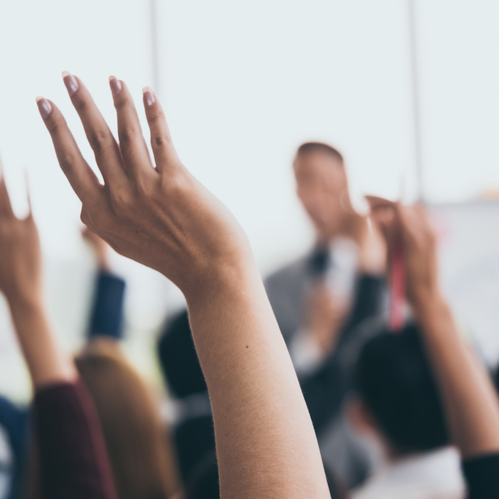 audience-raising-hands-up-while-businessman-is-spe