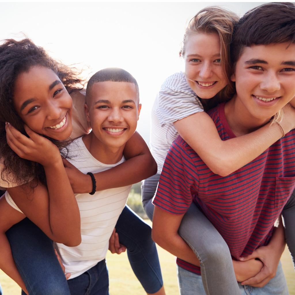 teenage-school-friends-having-fun-piggybacking-out