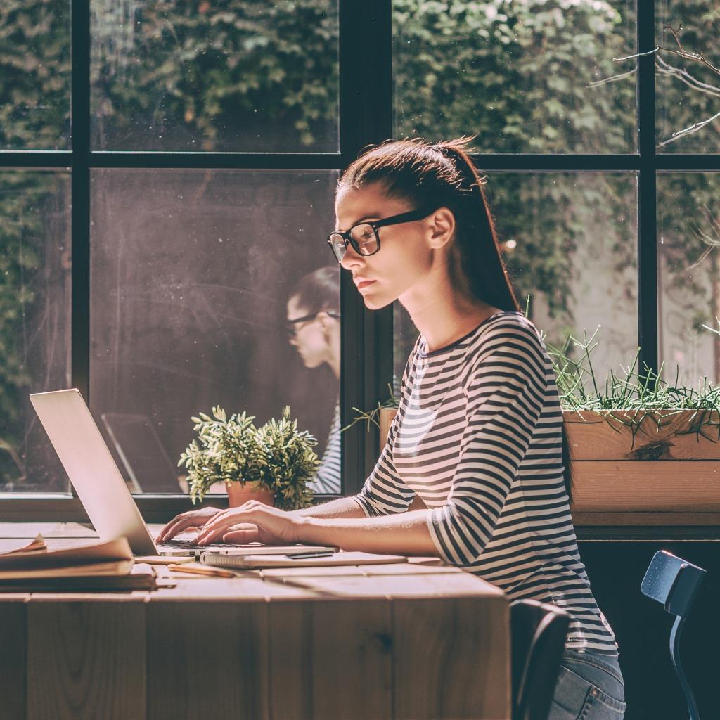 woman at computer sitting at table at home