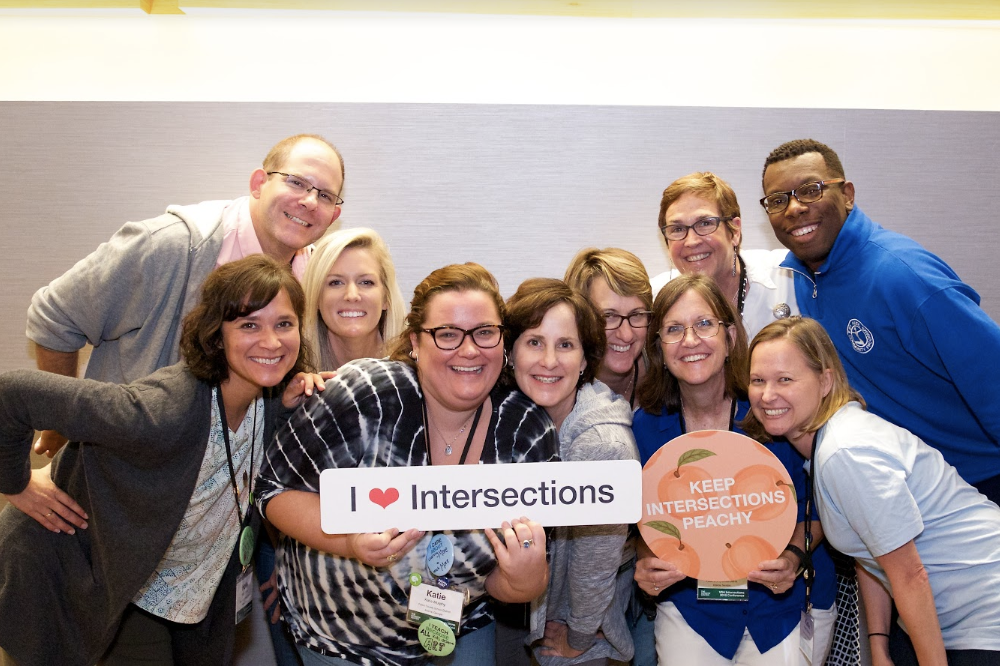 "A group of teachers are clustered together and smile at the camera. They are holding two signs that say ""I (heart) Intersections"" and ""Keep Intersections Peachy."""
