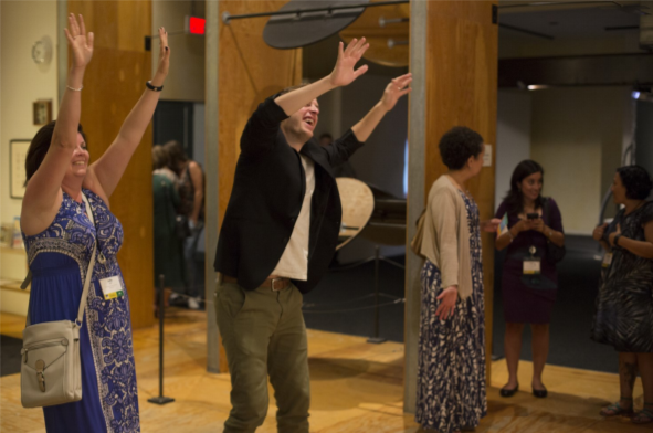Several conference attendees are standing in the back of a conference session room, two of the attendees are waving their arms in the air during an activity