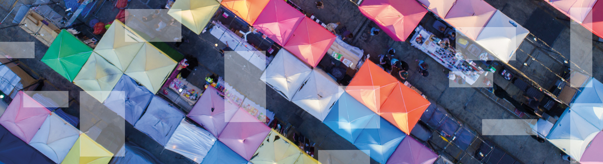 Vibrant colored, pop-up vendor tents with people shopping