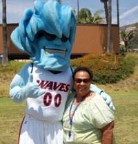 An alumnus poses with mascot Willie the Wave during Family Camp - Pepperdine University